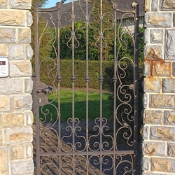 An exclusive wrought iron gate and fence in a family villa - A historical gate